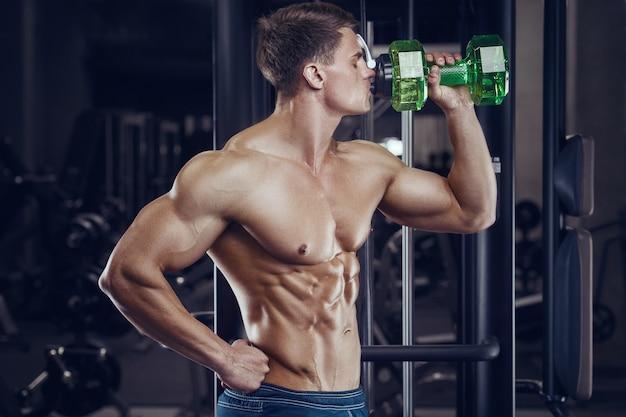 Culturista bebiendo agua después del entrenamiento físico