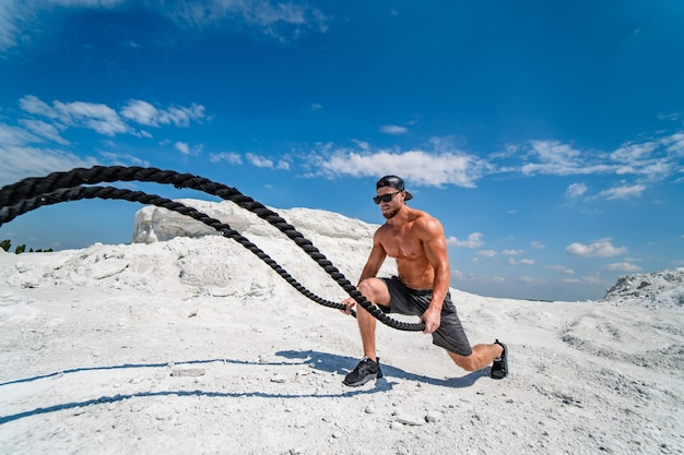 Culturista brutal fuerte bombeo de los músculos. entrenamiento con cuerdas. concepto de culturismo y deportes al aire libre. posando al aire libre. entrenamiento en una cantera. vista lateral. paisaje blanco.