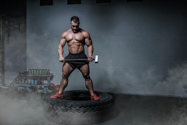 Culturista brutal hombres atléticos fuertes entrena en el gimnasio