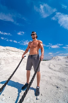 Culturista fuerte con una gorra y gafas de sol entrenando con cuerdas al aire libre. entrenamiento pesado en una cantera. paisaje blanco.