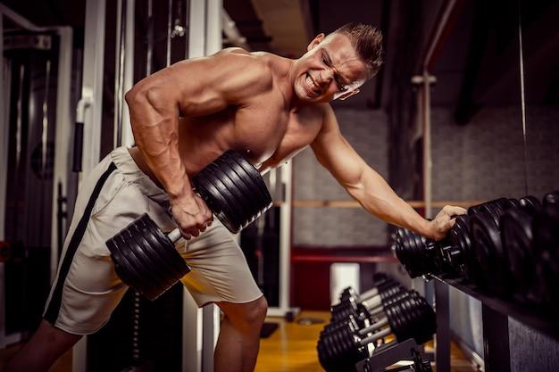 Culturista fuerte haciendo ejercicio pesado para la espalda