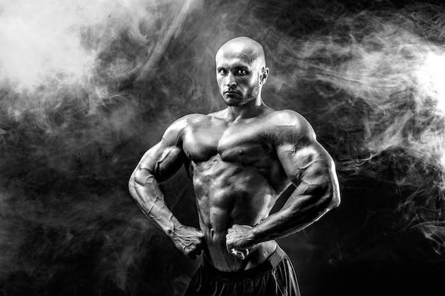 Culturista fuerte posando y mostrando músculos
