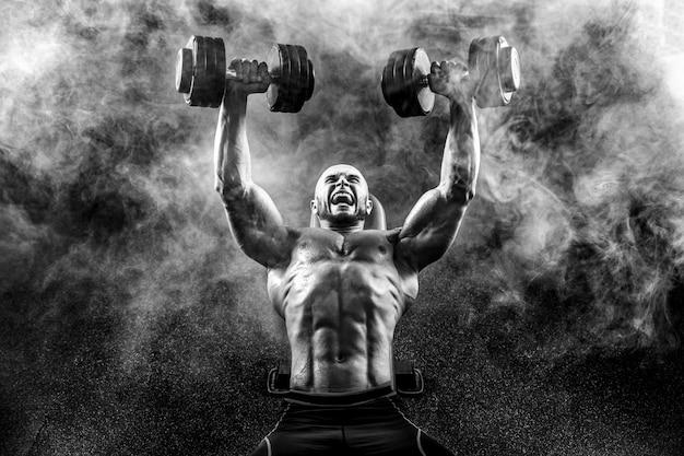 Culturista fuerte posando y sosteniendo pesas
