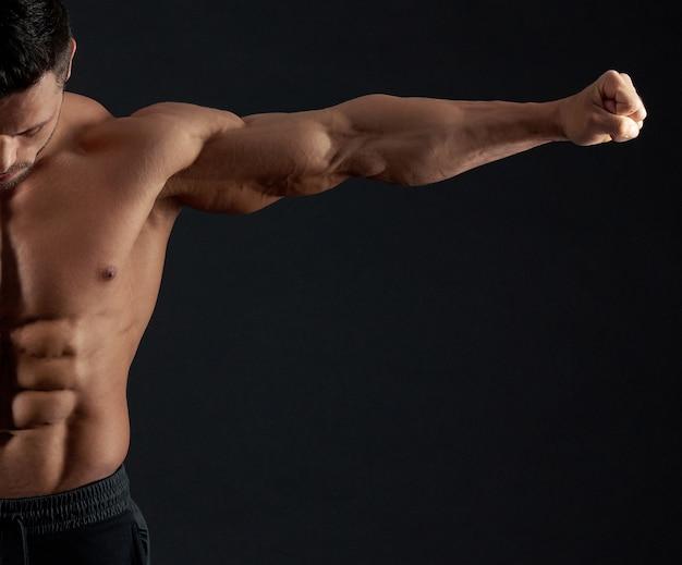 Culturista fuerte que demuestra los músculos de su brazo