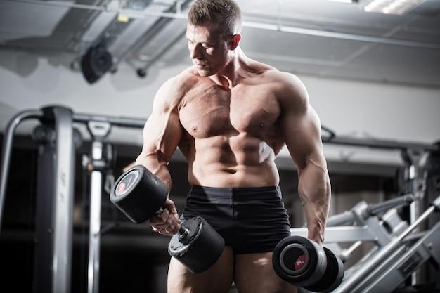 Culturista en gimnasio en entrenamiento físico con pesas