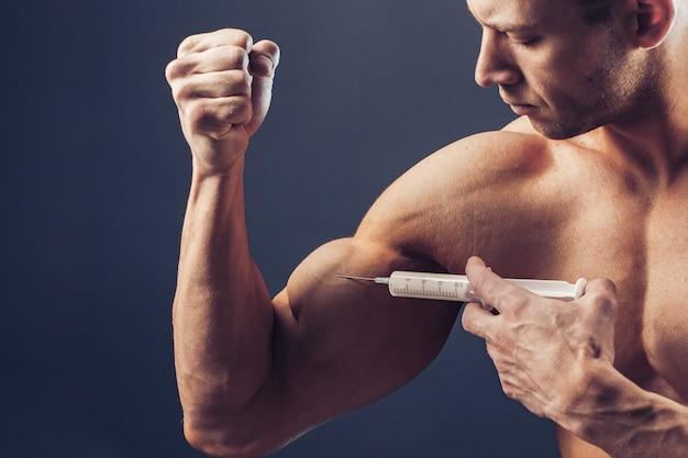 Culturista hace la inyección de vitaminas. foto de hombre deportivo con físico perfecto sobre fondo oscuro. fuerza y motivación
