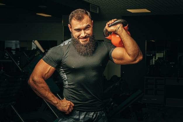 Culturista haciendo ejercicios con pesas en un gimnasio oscuro