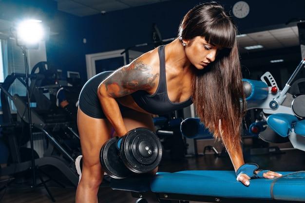 Culturista joven haciendo pesas tira en un gimnasio