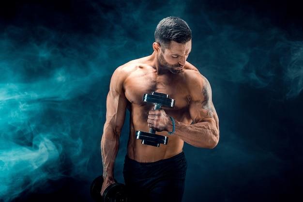 Culturista joven rasgado con abdominales perfectos, hombros, bíceps, tríceps y cofre posando con una pesa