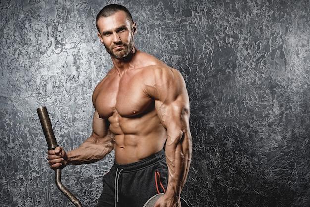 Culturista muscular que ejercita con una barra