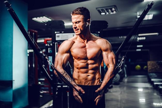 Culturista musculoso trabajando en el gimnasio haciendo ejercicios para volar el pecho en la máquina de cable