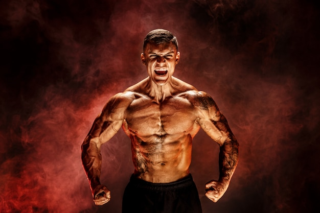 Culturista posando fitness hombre musculoso tatuado en escena de humo rojo