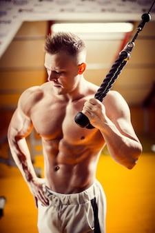 Culturista preparándose para hacer ejercicio con barra en el gimnasio