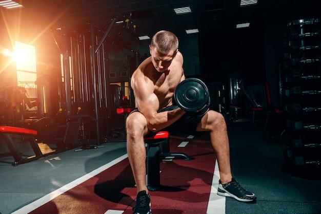 Culturista profesional, ejercicios con pesas en el gimnasio, entrenamiento en los bíceps. motivación.