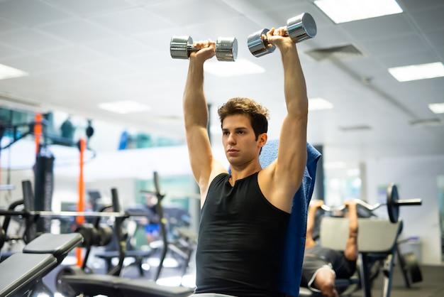 Culturista usando una pesa para hacer ejercicio en un gimnasio