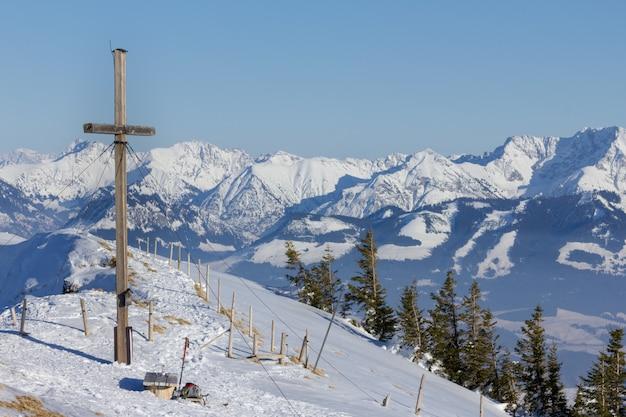 Cumbre cruzada en invierno con vistas a una cadena montañosa.