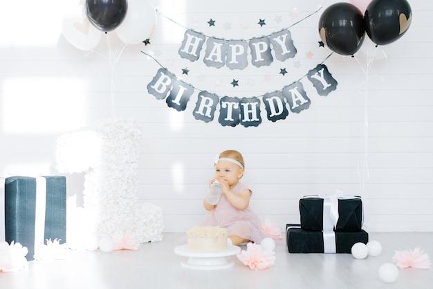Cumpleañera 1 año sentada en la zona de fotos rodeada de regalos, flores.