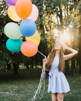 Cumpleañera de ángulo bajo con globos en la luz del sol