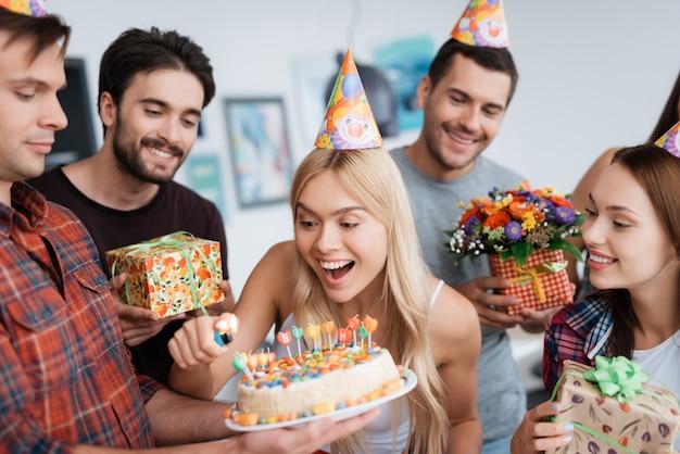 Cumpleañera enciende velas. hombre espera pastel de cumpleaños.