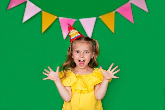 Cumpleañera joven en blusa amarilla con gorra riendo sobre fondo verde con espacio de copia. muy feliz.