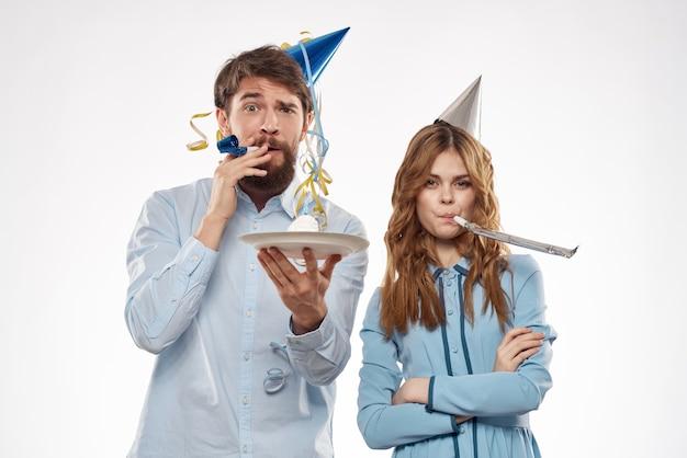 Cumpleaños hombre y mujer con un cupcake y una vela en un gorro de fiesta, fondo blanco.