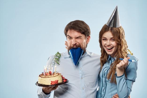 Cumpleaños hombre mujer con sombreros de fiesta sobre un fondo azul.