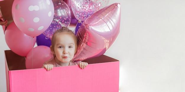Cumpleaños infantil. hermosa niña colocada en una gran caja de regalo rosa con globos