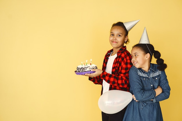 Cumpleaños de niñas aislado en la pared amarilla. niños sosteniendo pastel.