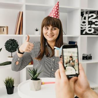 Cumpleaños de streaming de blogger femenina sonriente con smartphone