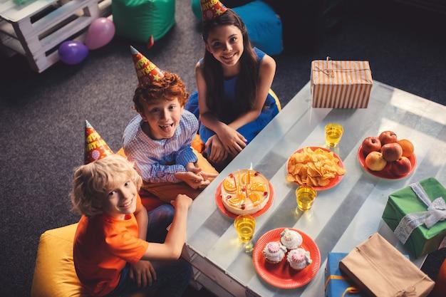 Cumpleaños. tres niños sentados a la mesa con comida dulce.