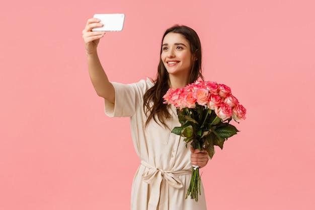 Cumpleaños, vacaciones, concepto de romance. encantadora mujer caucásica joven y atractiva recibe la entrega, recibió flores de regalo, se autofoto en el teléfono inteligente con un hermoso ramo, de pie feliz pared rosa
