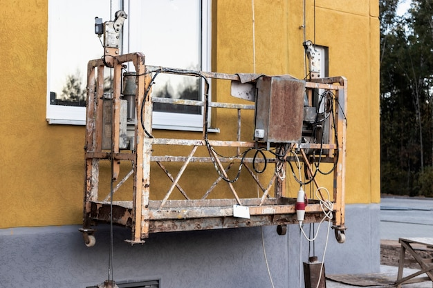 Cuna de construcción profesional o góndola para trabajos de construcción en altura de un edificio de gran altura. equipos industriales para trabajos en altura.