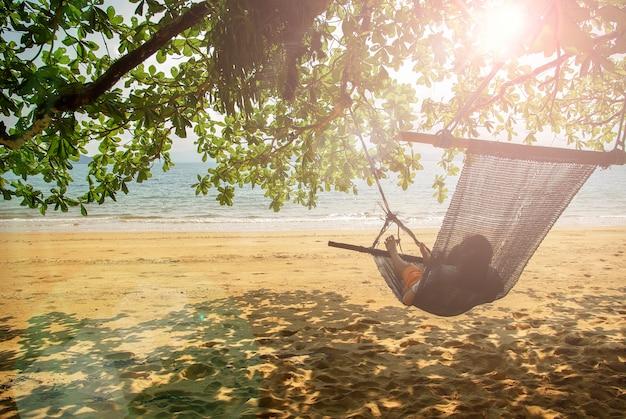 Cuna de playa bajo el árbol junto a la playa.