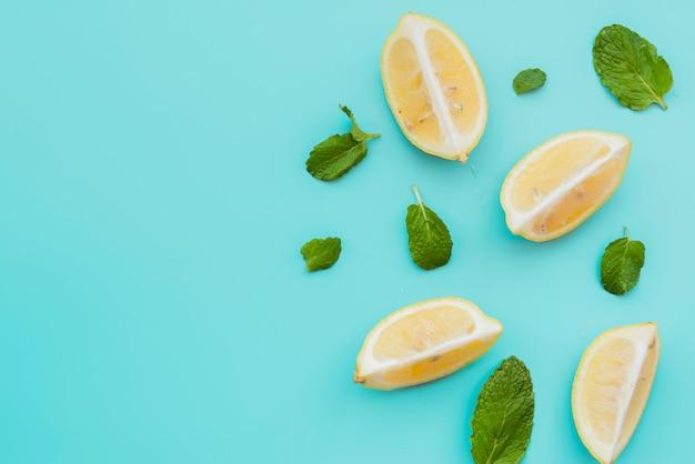 Cuñas de limón y hojas de menta sobre fondo