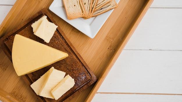 Cuñas de queso triangular en bandeja de madera contra el escritorio blanco