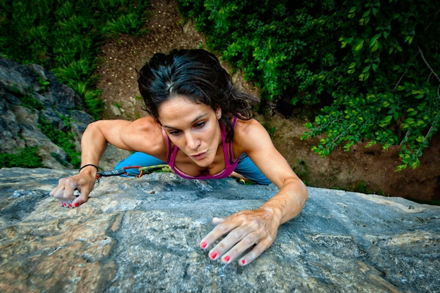 Cuota escalando en la roca de una hermosa niña