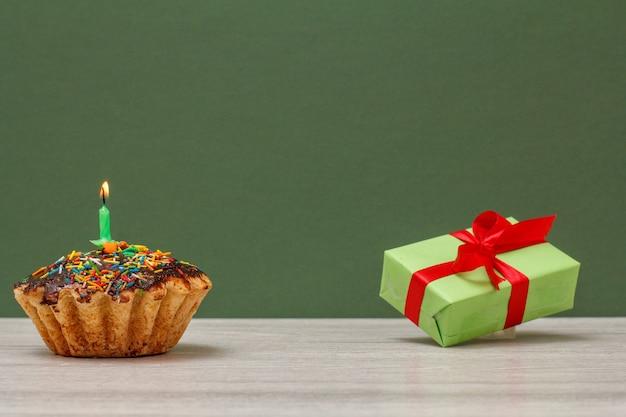 Cupcake de cumpleaños con glaseado de chocolate y caramelo, decorado con velas festivas encendidas y caja de regalo sobre fondo verde. concepto de feliz cumpleaños.