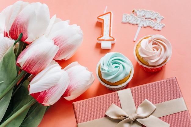 Cupcake de cumpleaños con regalo y flores