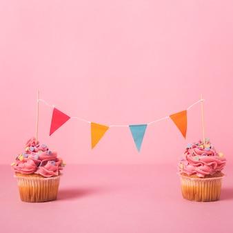 Cupcake de cumpleaños rosa con guirlanda