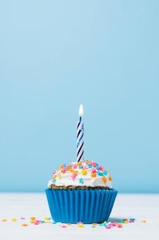 Cupcake de cumpleaños con velas sobre fondo azul.