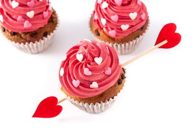 Cupcake decorado con corazones de azúcar y una flecha de cupido para el día de san valentín aislado sobre fondo blanco.