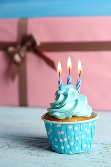 Cupcake dulce con vela en la mesa de madera azul contra rosa cajas presentes