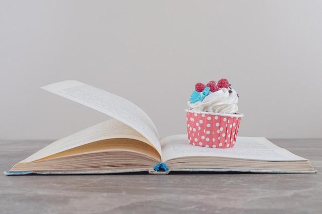 Un cupcake y un libro abierto sobre mármol.