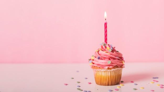 Cupcake rosa con vela encendida