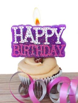 Un cupcake con velas encendidas feliz cumpleaños aislado sobre fondo blanco.