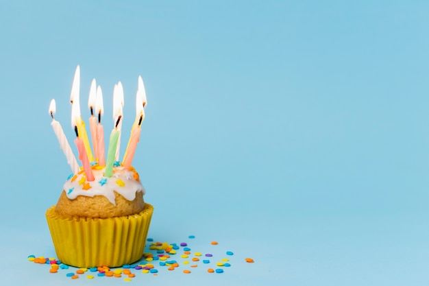 Cupcake con velas encendidas sobre fondo azul con espacio de copia