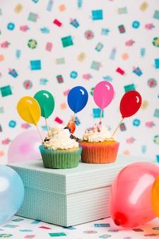 Cupcakes con adornos de globos brillantes en caja