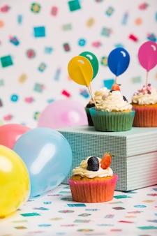 Cupcakes con adornos de globos de papel en caja