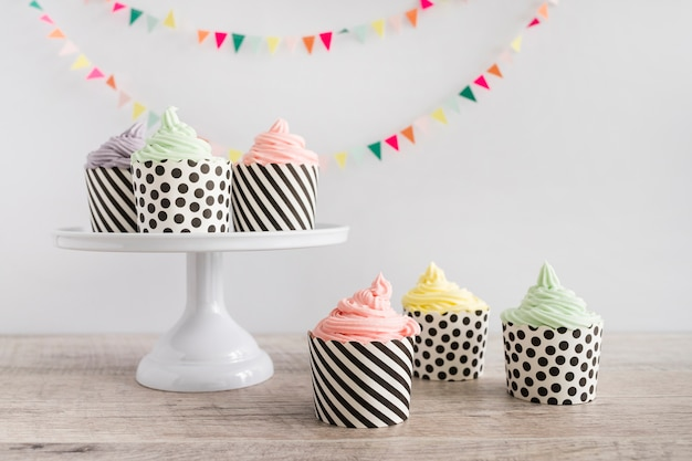Cupcakes buttercream color pastel delante de banderines