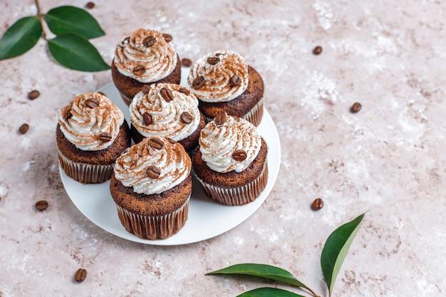 Cupcakes de café decorados con crema batida y granos de café.